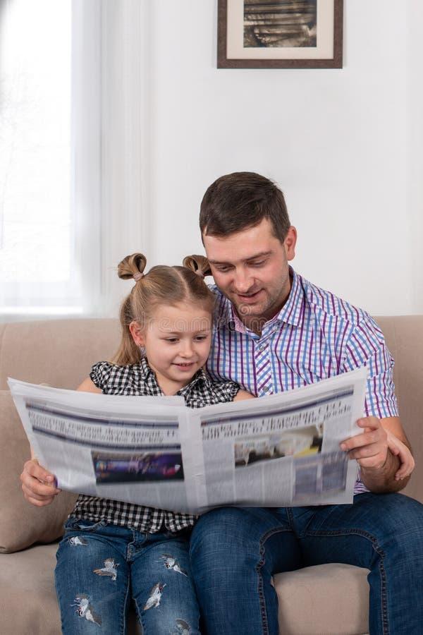 O estúdio disparou de uma menina e de seu paizinho que sentam-se no sofá em casa e que leem o jornal junto imagens de stock
