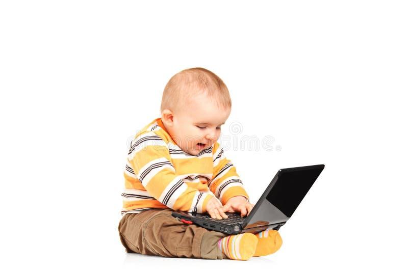 O estúdio disparou do bebé que trabalha em um portátil foto de stock royalty free