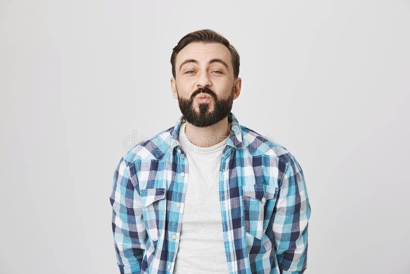 O estúdio disparou do homem adulto atrativo engraçado com barba, dobrando os bordos ao esperar o beijo e ao ser entusiasmado, pos foto de stock royalty free