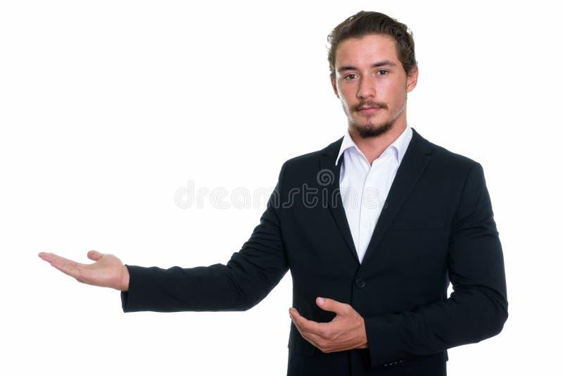 O estúdio disparou do homem de negócios considerável novo que mostra a algo o isolador fotos de stock royalty free