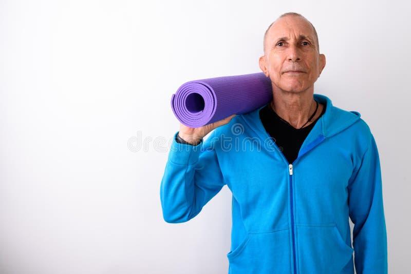 O estúdio disparou do homem superior calvo que mantém a esteira da ioga pronta para gym AG fotos de stock