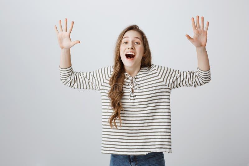 O estúdio disparou do modelo fêmea atrativo positivo que aumenta as palmas altamente e que ri para fora ruidosamente, jogando ou  fotografia de stock