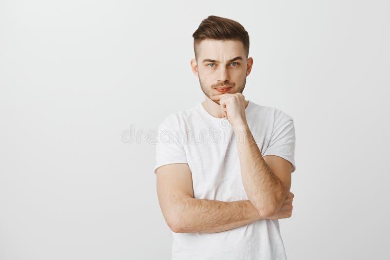 O estúdio disparou do modelo masculino à moda incerto intenso com penteado fresco em amuar olhando de sobrancelhas franzidas do t imagens de stock