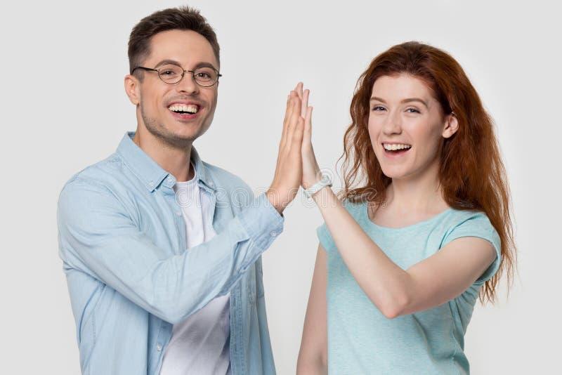 O estúdio disparou nos pares milenares felizes que dão um gesto de altamente cinco mãos foto de stock