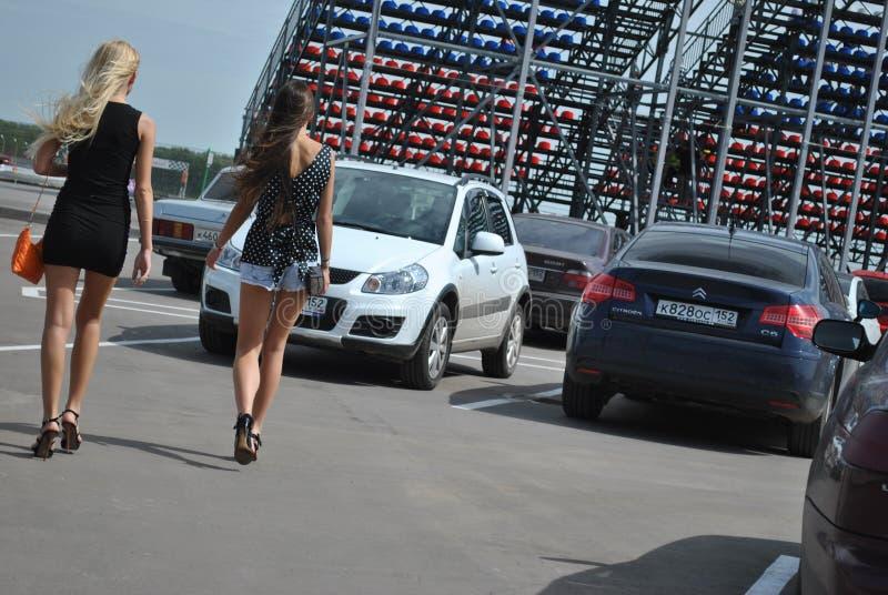 O estacionamento do carro em meninas das raças vai em saias curtos Competições de ajustamento de Sportscar em carros ajustados na imagens de stock