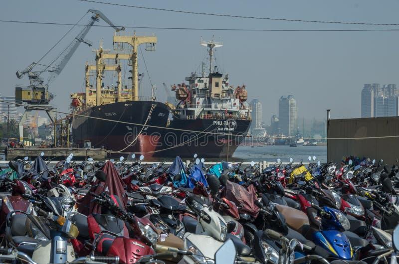 O estacionamento dos velomotor aproxima o rio, com navios de carga fotografia de stock