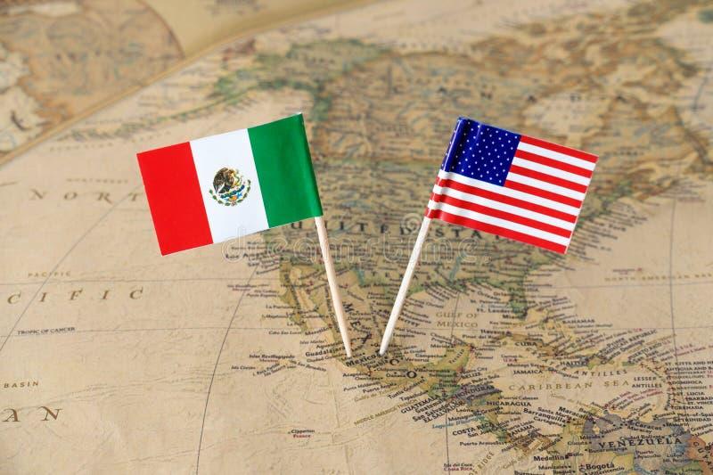 O Estados Unidos da América e o México embandeiram os pinos em um mapa do mundo, conceito das relações políticas imagens de stock royalty free