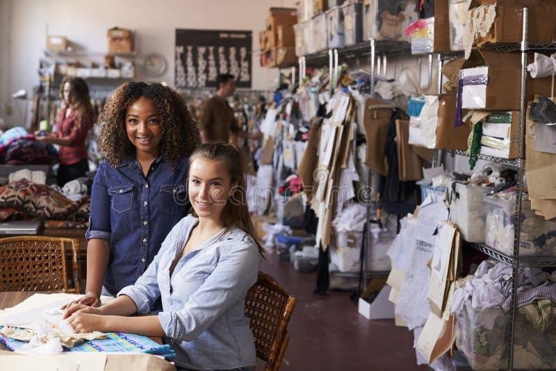 O estagiário e o gerente no estúdio do projeto da roupa olham à câmera imagem de stock royalty free