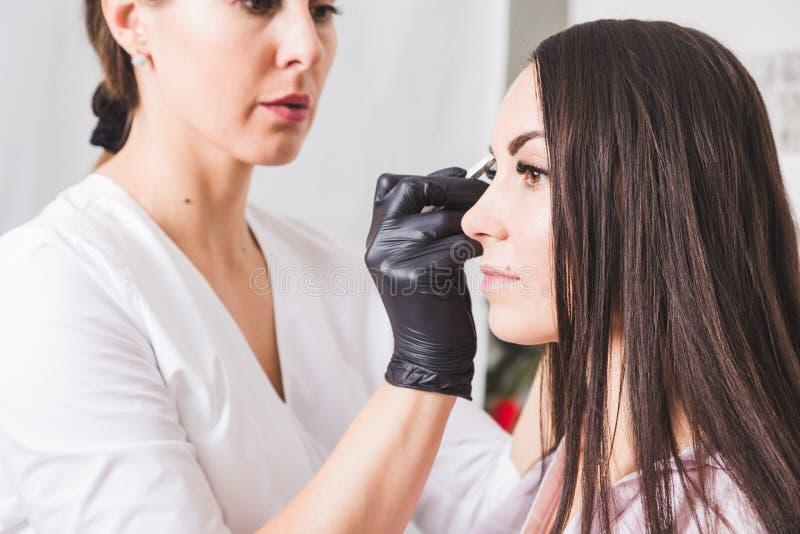 O esteticista arranca as sobrancelhas de uma jovem mulher com pinça fotos de stock