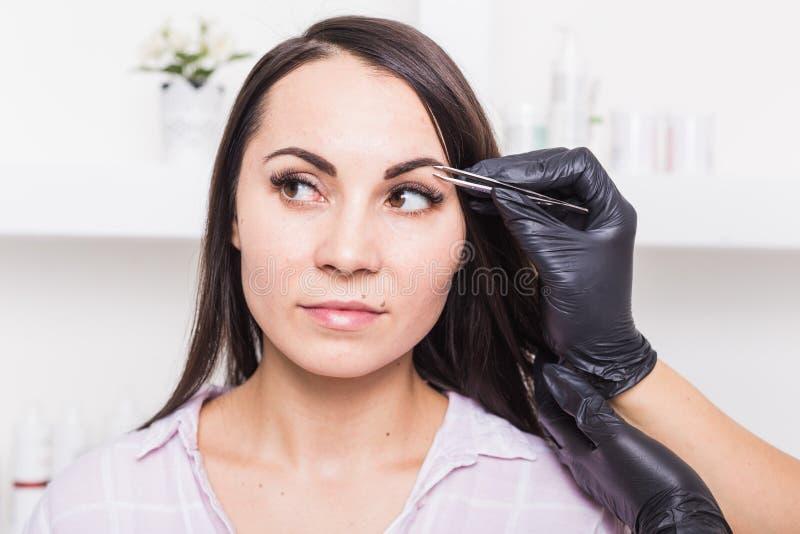 O esteticista arranca as sobrancelhas de uma jovem mulher com pinça imagem de stock