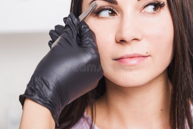 O esteticista arranca as sobrancelhas de uma jovem mulher com pinça imagem de stock royalty free