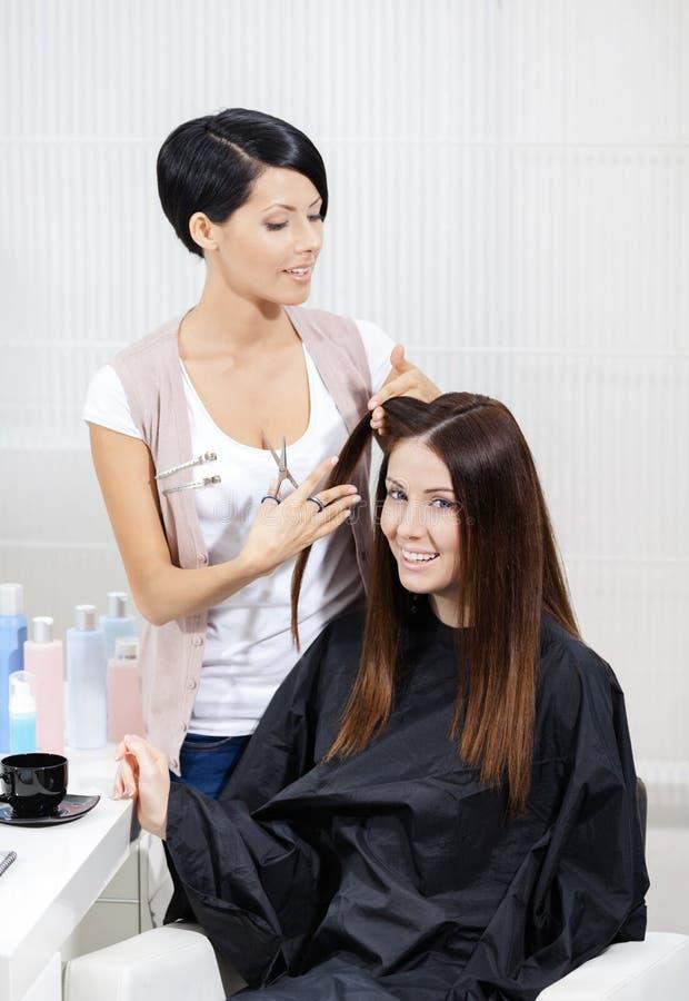 O esteticista corta o cabelo da mulher no salão de beleza do cabeleireiro fotos de stock