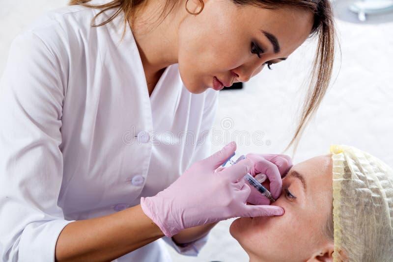 O esteticista empurra uma seringa para injetar Botox imagem de stock royalty free