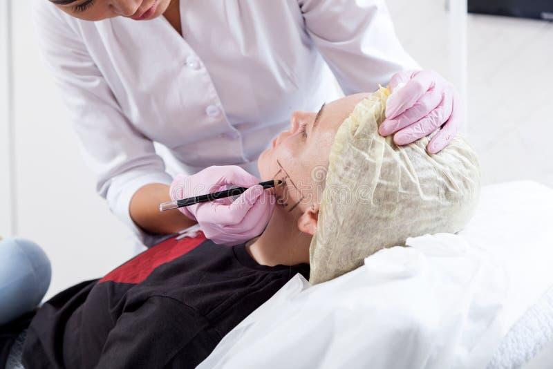 O esteticista empurra uma seringa para injetar Botox foto de stock
