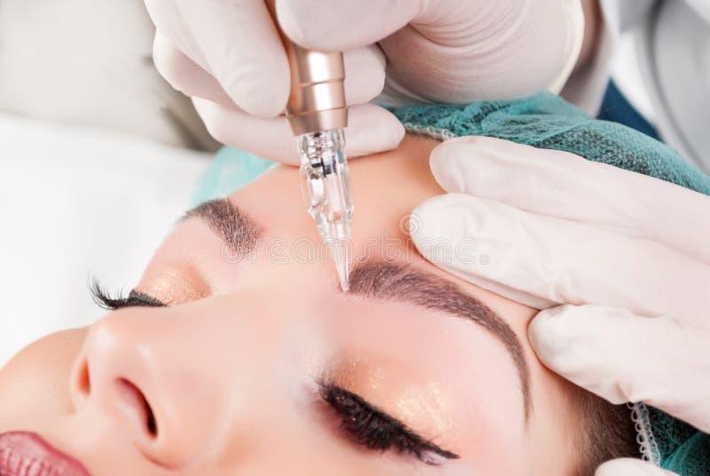 O esteticista entrega fazer a tatuagem da sobrancelha na cara da mulher fotos de stock