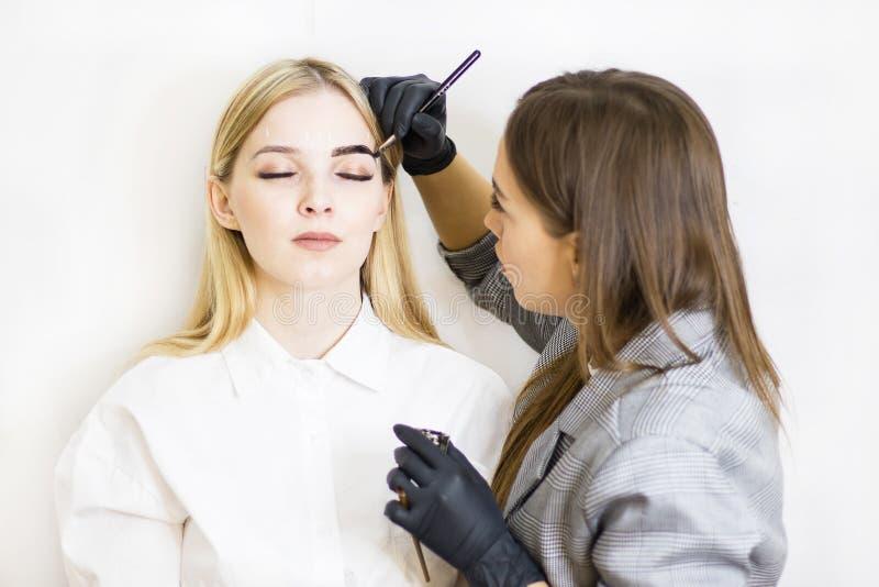 O esteticista executa a correção da sobrancelha em um modelo bonito em um salão de beleza A menina ? loura Tratamento facial Ting imagens de stock royalty free