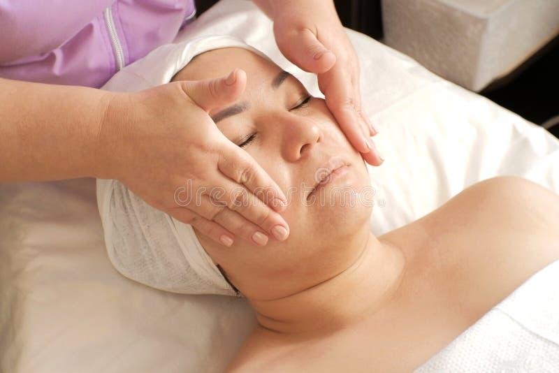O esteticista negocia o creme hidratante na cara da mulher Máscara da beleza e da saúde cosmetology Cuidado facial Close-up fotos de stock royalty free