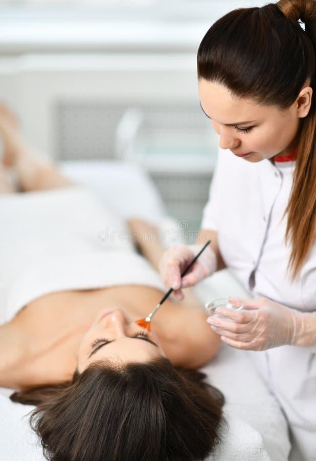 O esteticista novo prepara a cara do paciente para um procedimento cosmético aplicando uma composição especial com uma escova imagens de stock