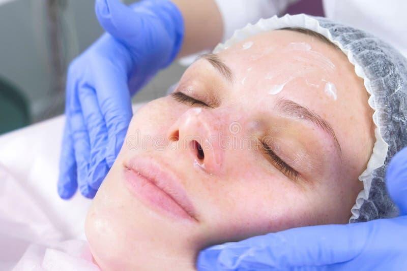 O esteticista põe o creme sobre a cara da mulher Tratamento facial do Cosmetologist Close-up fotografia de stock royalty free