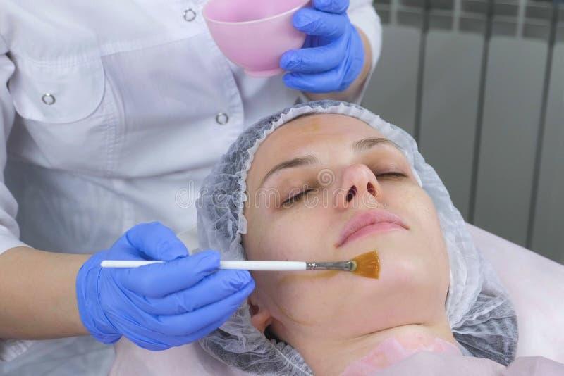 O esteticista põe uma máscara sobre a cara da mulher com uma escova Mãos de um cosmetologist em luvas de borracha azuis facial fotos de stock royalty free