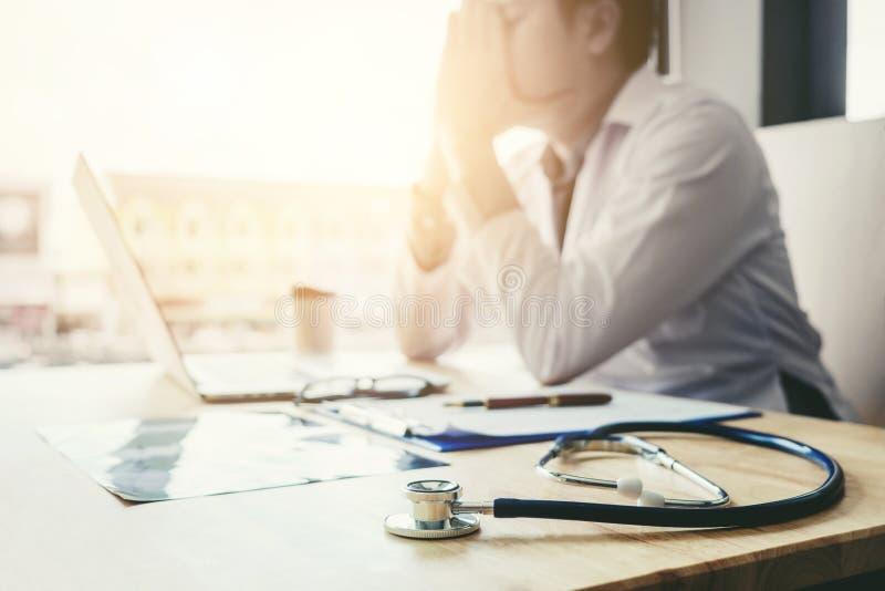 O estetoscópio e o doutor que sentam-se com portátil forçam o abou da dor de cabeça imagem de stock