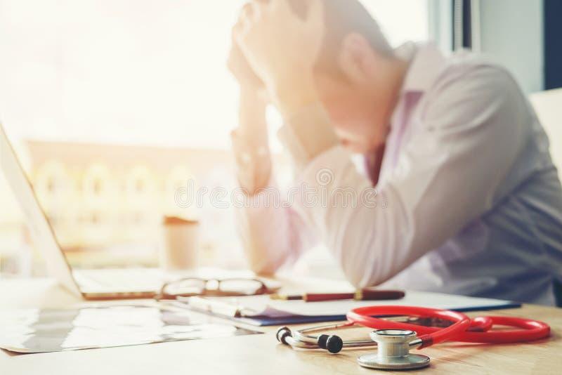O estetoscópio e o doutor que sentam-se com portátil forçam a dor de cabeça aproximadamente foto de stock