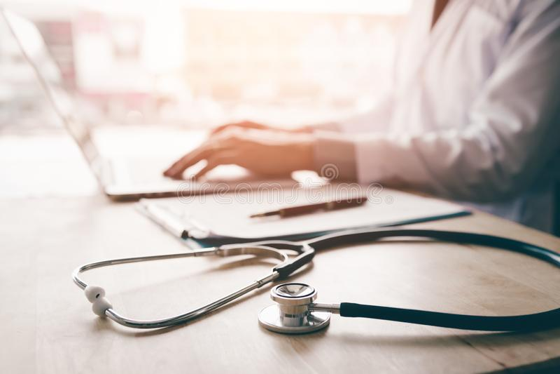 O estetoscópio e o fundo medicam usando o portátil na mesa na clínica fotografia de stock royalty free
