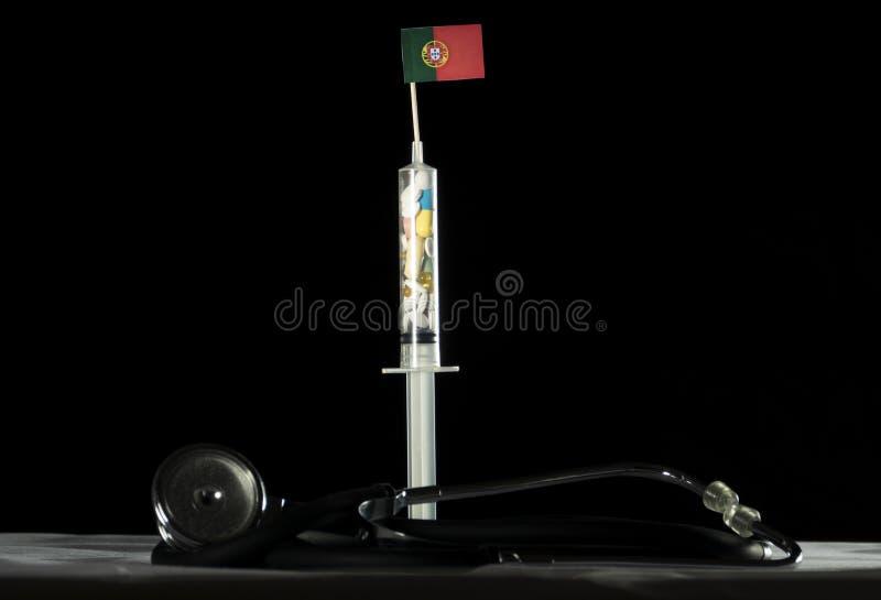 O estetoscópio e a seringa encheram-se com as drogas que injetam o Portugue imagens de stock royalty free