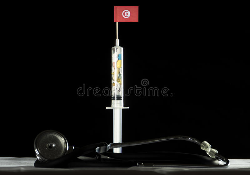 O estetoscópio e a seringa encheram-se com as drogas que injetam o Tunisian imagem de stock