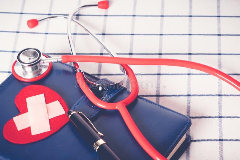 O estetoscópio vermelho dos cuidados médicos do dia de saúde de mundo e do conceito médico e o coração vermelho dão forma no cade foto de stock