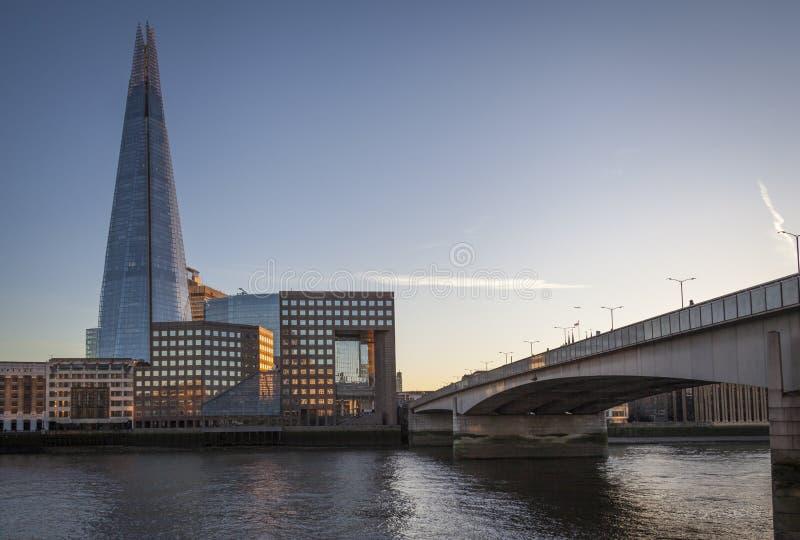 O estilhaço e a ponte de Londres pelo rio Tamisa durante o por do sol imagens de stock