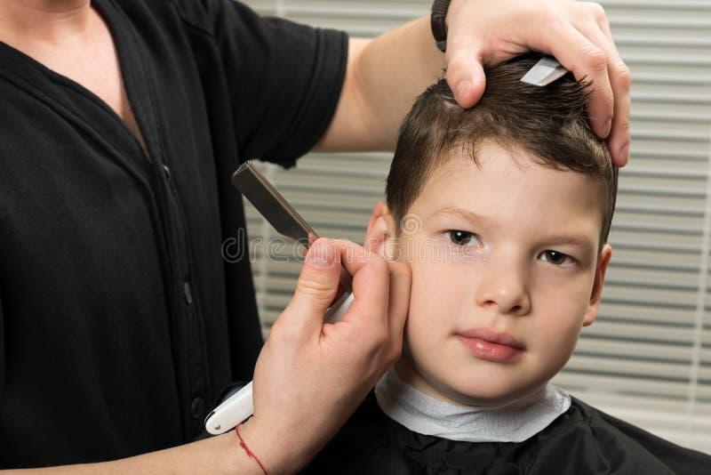 O estilista faz ao menino um penteado no salão de beleza fotos de stock royalty free