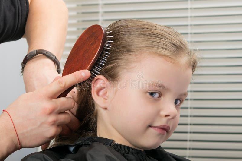 O estilista faz o cabelo que denomina na cabeça com um pente para uma menina de sorriso pequena foto de stock royalty free