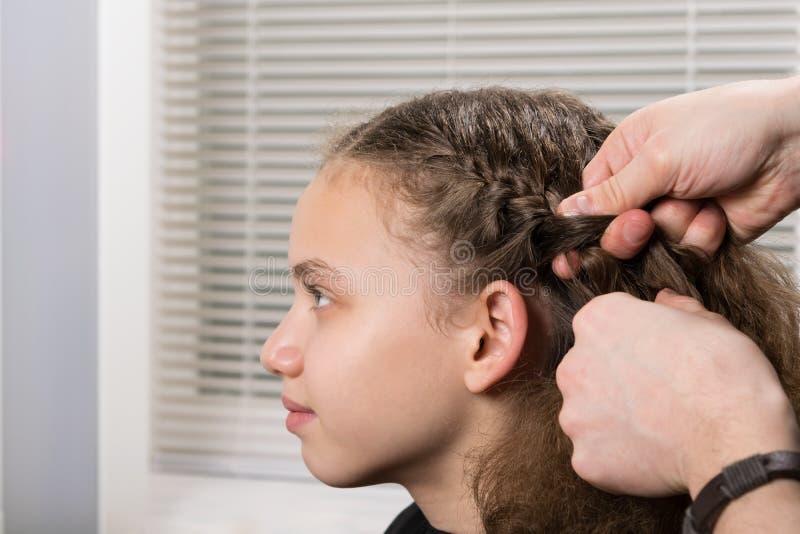 O estilista faz um penteado da menina da trança no salão de beleza foto de stock