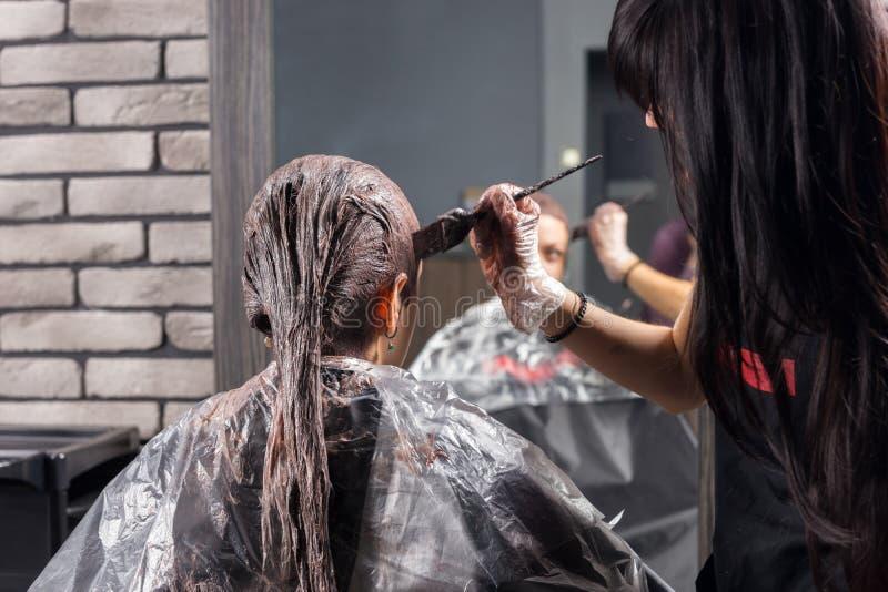 O estilista novo estão e o processo dos revestimentos de tingir o cabelo do youn imagens de stock