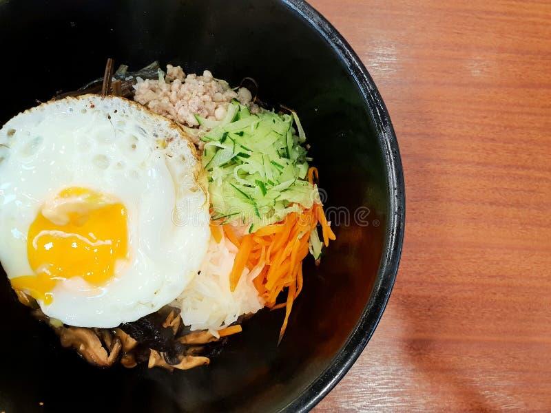 O estilo coreano do alimento, vista superior do arroz é coberto com vegetais temperados, carne e lado acima do ovo frito na parte foto de stock