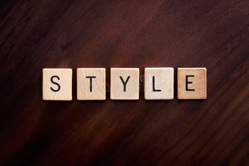 O estilo da palavra soletrou para fora em blocos de madeira da letra no fundo de madeira escuro imagem de stock