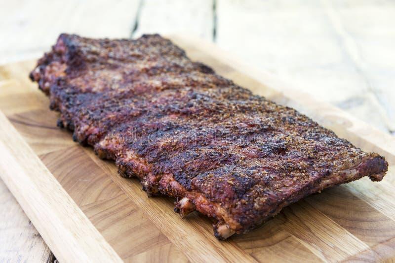 O estilo de St Louis grelhou reforços de carne de porco na placa de corte imagens de stock royalty free