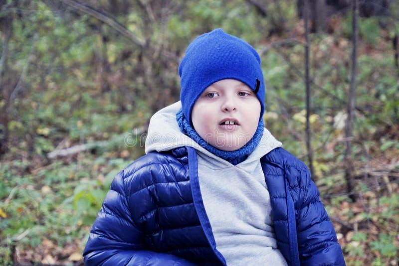 O estilo de vida, a criança autística no chapéu azul e o casaco azul que joga com as folhas murchadas no outono estacionam para u foto de stock