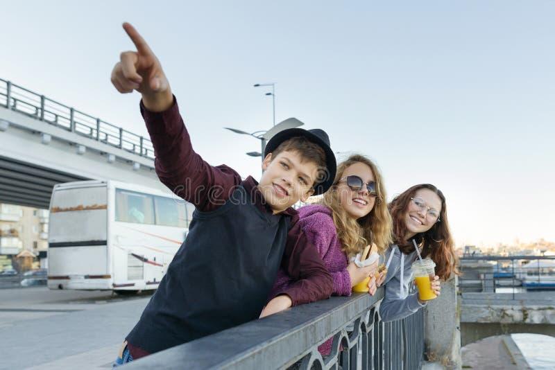 O estilo de vida dos adolescentes, o menino e duas meninas adolescentes estão andando na cidade Rindo, crianças de fala que comem fotografia de stock royalty free