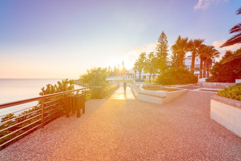 O estilo de vida saudável ostenta a mulher que corre no beira-mar de madeira do nascer do sol do passeio à beira mar imagem de stock