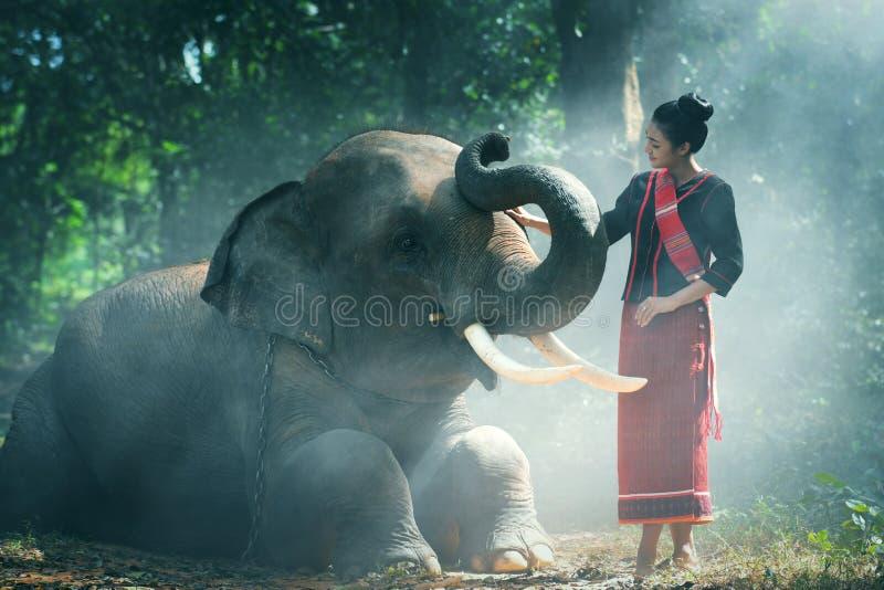 O estilo do nordeste da mulher tailandesa nova bonita ? apreciar dan?ar e jogar com o elefante na selva imagens de stock