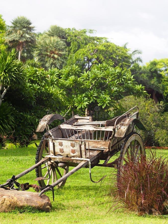 O estilo retro do vintage usou o carro de madeira do metal que está no jardim da grama verde fotos de stock royalty free