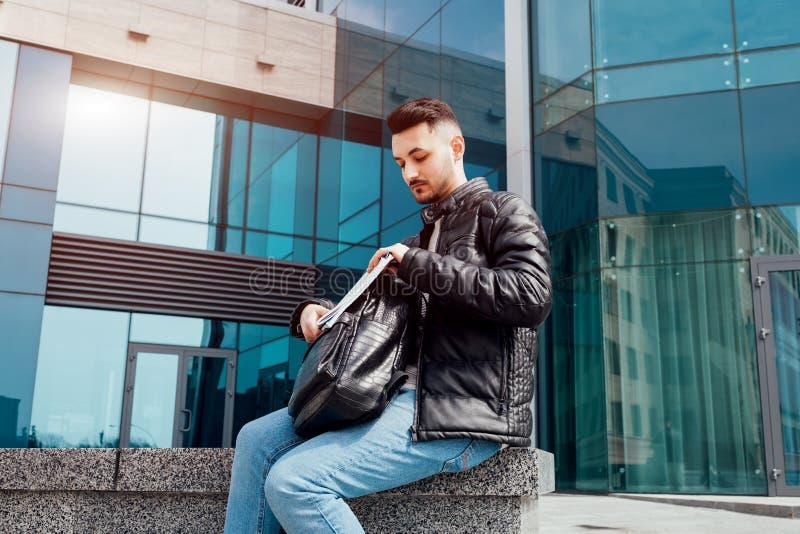 O estudante árabe toma seus cadernos fora da trouxa fora Homem novo que senta-se pela universidade moderna imagens de stock royalty free