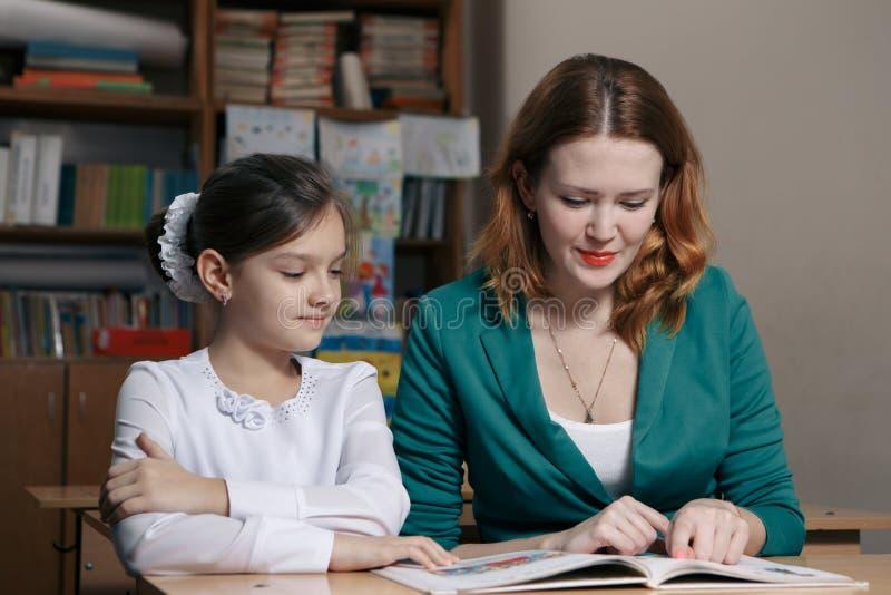 O estudante é tutoria um a escola primária imagens de stock royalty free