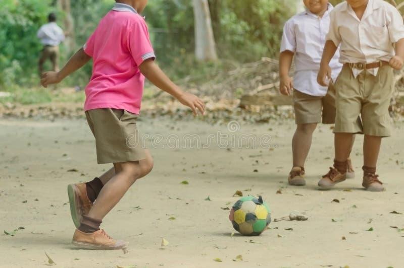 O estudante aprecia para jogar o futebol velho com seus amigos na terra fotos de stock royalty free