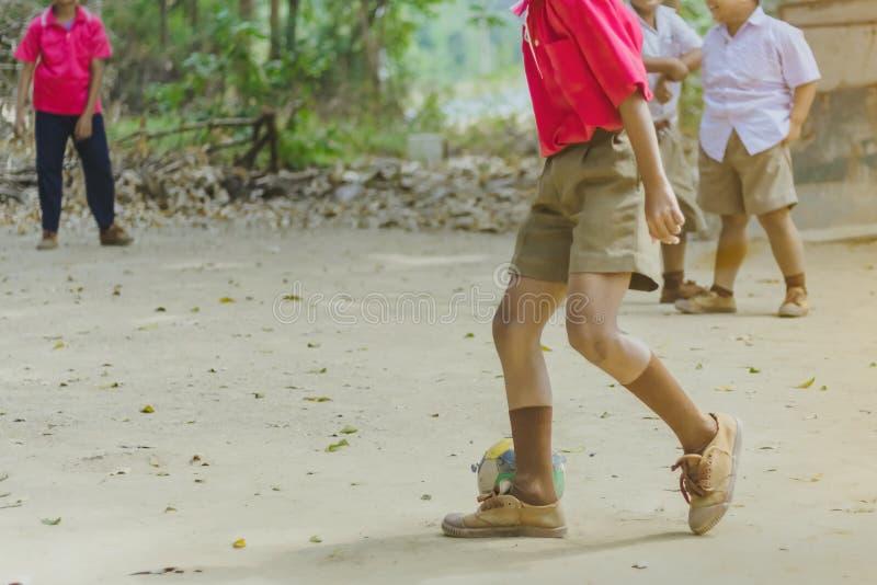 O estudante aprecia para jogar o futebol velho com seus amigos na terra imagens de stock royalty free