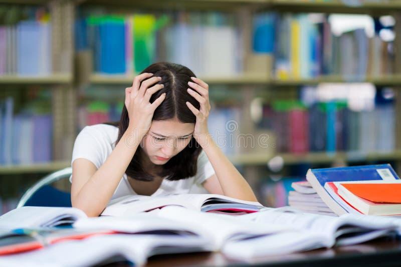 O estudante asiático da senhora leu um livro antes do exame fotografia de stock