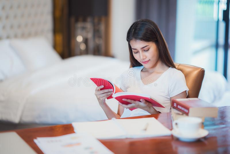 O estudante asiático da senhora leu um livro de texto para prepara-se ao exame o imagens de stock royalty free