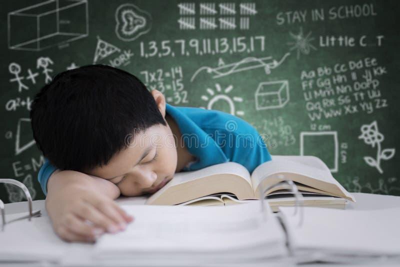 O estudante asiático do preteen parece cansado na sala de aula imagem de stock